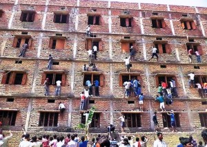 FILE - In this Wednesday, March 18, 2014 file photo, Indians climb the wall of a building to help students appearing in an examination in Hajipur, in the eastern Indian state of Bihar. Education authorities in eastern India say 600 high school students have been expelled after they were found to have cheated on pressure-packed 10th grade examinations. (ANSA/AP Photo/Press Trust of India, File) INDIA OUT