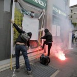 Demonstrators throw paint on a bank window during a protest against the Milan's Universal Exposition, EXPO2015 in Milan, 01 May 2015.    ANSA/MASSIMO PERCOSSI