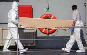 Rescuers carry a coffin off the Irish military vessel Naimh  after its arrival in the port of Palermo on August 6, 2015, with 367 survivors aboard and 25 coffins, following a rescue operation at sea of  a boat carrying over 600 migrants that capsized in the Mediterranean Sea off the Libyan coast. Survivors of a shipwreck off the coast of Libya in which some 200 migrants were feared drowned were being brought to safety in Sicily on August 6, as tales emerged of the 'horrific' moment the boat overturned.   AFP PHOTO / MARCELLO PATERNOSTRO